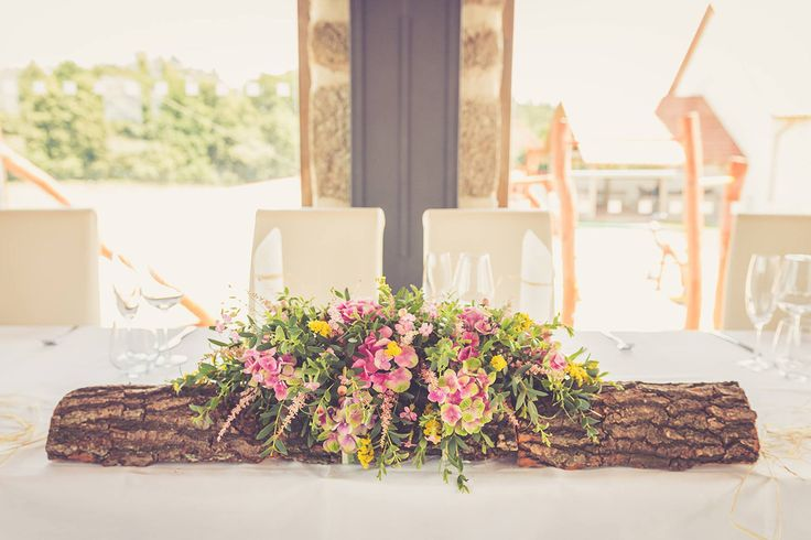 A rustic flower centerpiece attached to a wooden plank. Incredibly romantic! Flower designer Klara Uhlirova.