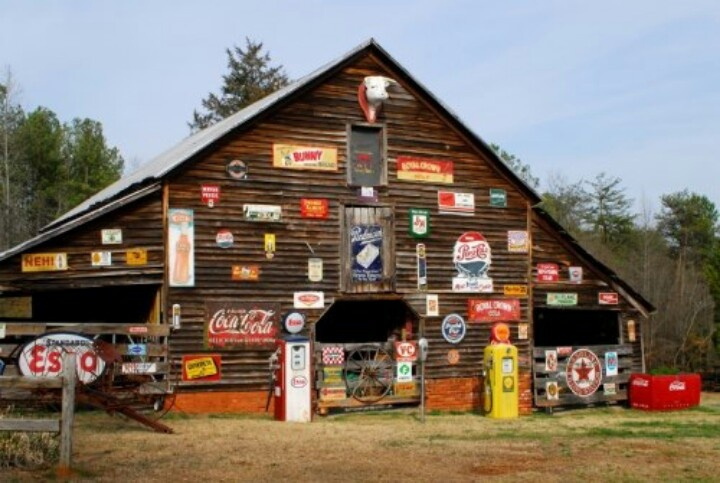 Barn With Display Of Vintage Advertising Signs Near