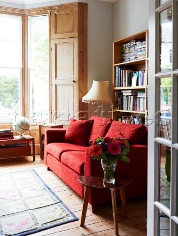 Red sofa and bay window in living room of colourful London home  England  UK