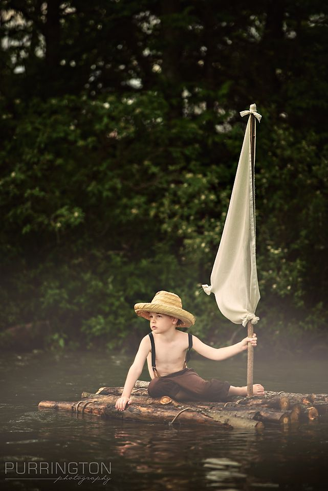 Beautiful fun creative photo shoot for young boy with a tom sawyer huckleberry finn theme on the lake river raft with a wood raft and white sail and costume with suspenders and straw hat. Fine art child photographer © Purrington Photography www.PurringtonPhotography.com Bemidji Photographer