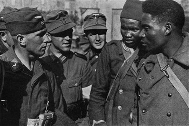 German soldiers talking with Nigerian French army POWs,  France 1940.