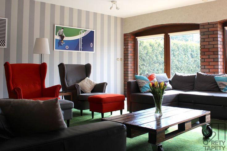 Pokój telewizyjny, stolik z palet, kolorowe fotele, tapeta w szare szerokie pasy.