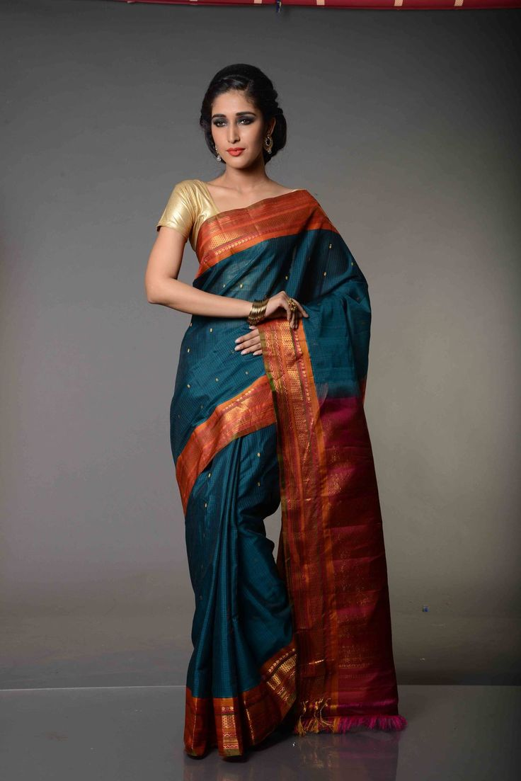 Nirupama English Blue and Rustic Magenta Cotton Gadwal Saree : Woven in cosmopolitan colors, with zari work in dull gold finish, Nirupama English Blue and Rustic Magenta Silk Cotton Gadwal Saree is grace personified. While the combination of English blue body and magenta color border looks breathtaking, the uniqueness of the sari lies in its pallu adorned in pretty pink, very unlike the Gadwal Sarees which have same colored pallu and border.
