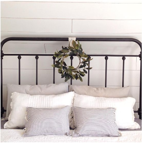 I am loving the stack of pillows and the charming wreath on this wrought iron bed frame!