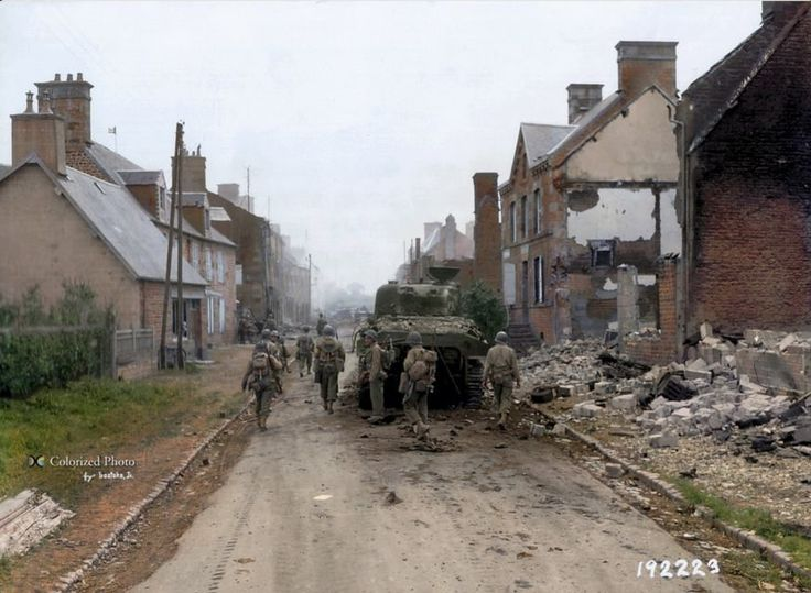 US troops of the 1/18th Infantry Regiment, 1st Infantry Division move down the main road in Mortain, Normandy in the direction of Avranches past a Sherman tank knocked out in earlier fighting, possibly a tank of the 32nd Armoured Regiment, 3rd Armoured Division that clashed with elements of the 116 Panzer Division in the town during the afternoon of the 2nd of August 1944