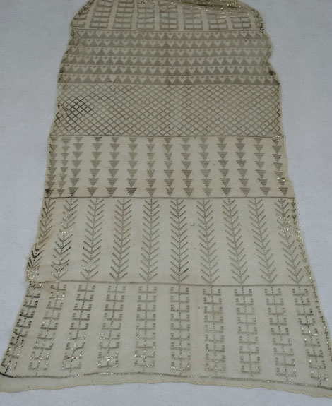 Assuit shawl, 1920s    Assuit cloth is a cotton mesh fabric embroidered with hammered metal pieces. The metal is wrapped around the mesh, and the ends are hammered under to hold the piece in place. (It makes me think of staples.) This type of cloth, produced since biblical times, is named for the Assuit region of Egypt, where it originated.