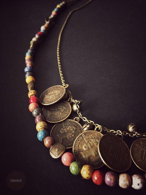 Collana realizzata con un filo di perline in ceramica dipinte a mano intervallate da perline in bronzo e da una catenina con piccole monetine da un penny alternate a campanellini in bronzo.