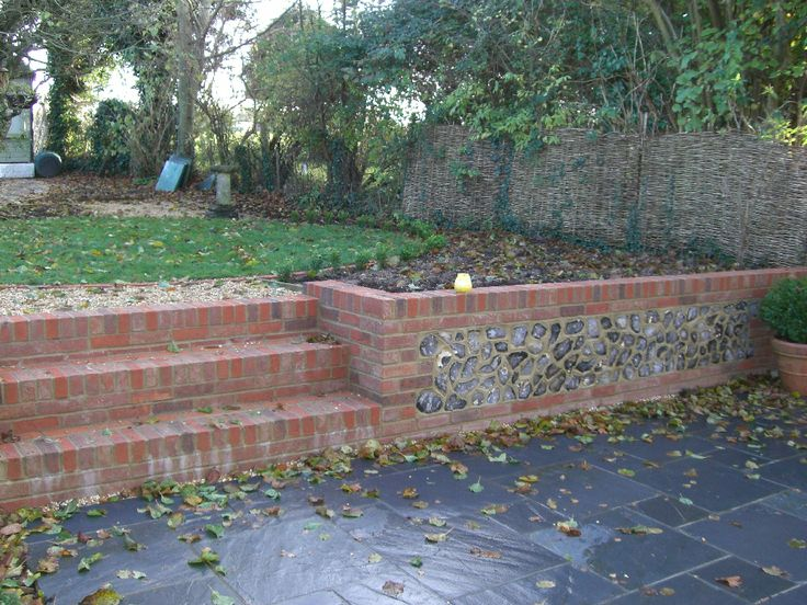 Slate patio with brick and flint retaining wall.