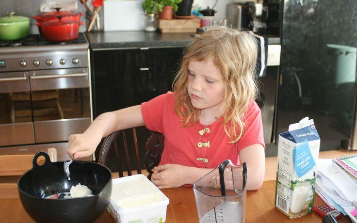 Annemijn doet de vanille ijs bij de aardbeien, bosbessen en melk voor de milkshake....