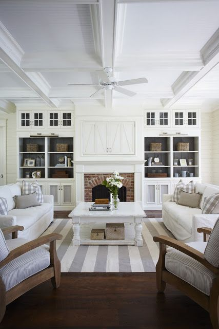 Light and neutral living room with a great striped rug. love the dark grey paint on the inside of the built in bookshelves