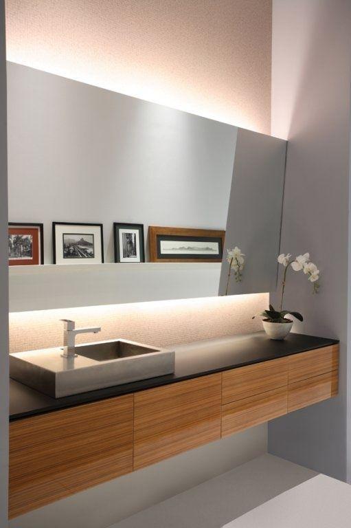 Banheiro de luxo com decoração simples: um espelho grande e uma bancada de madeira são ótimas opções!