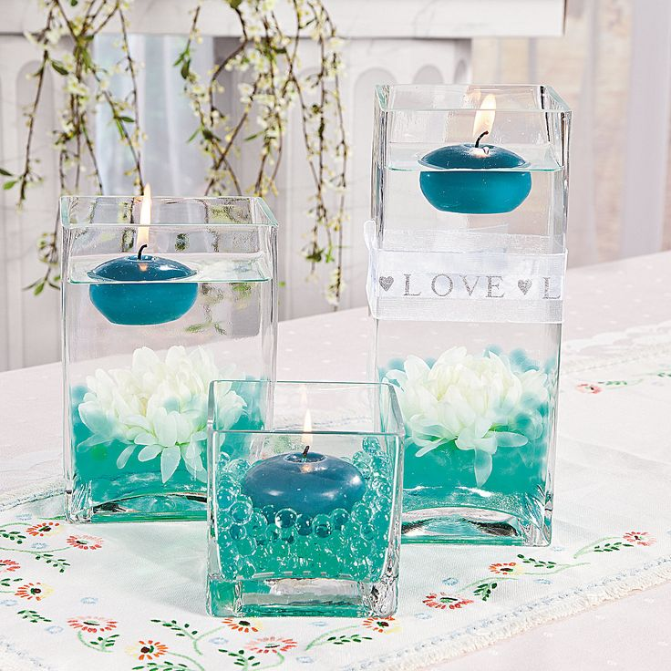 Floating Candle Centerpieces -Turquoise Water Beads  $2.00 Each Makes 1 1/2 quarts of hydrated water beads. Plastic. 2mm , Teal Floating Candles $12.75 Per Dozen OrientalTrading.com