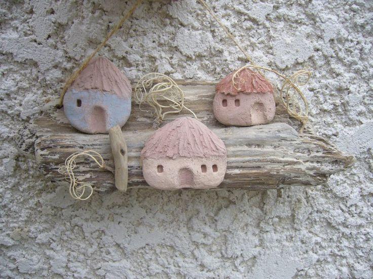 Petites maisons d'un village africain, 7 maisons miniatures en terre brune, portes et toits colorés, bleu, beige, rouge brique, badigeon clair sur les murs. Ces maisonnettes sont fixées sur un bois clair, un peu de végétation sur la pente. Décoration mura