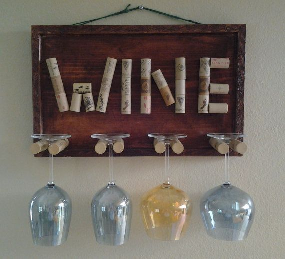 "I like the idea of using cork as the holders. I would probably decorate this with a painted saying rather than just putting ""Wine"" in cork. Could also use as a good idea for mugs with different handles... Decorative Wine Glass Holder by GulfCoasters on Etsy, $45.00"