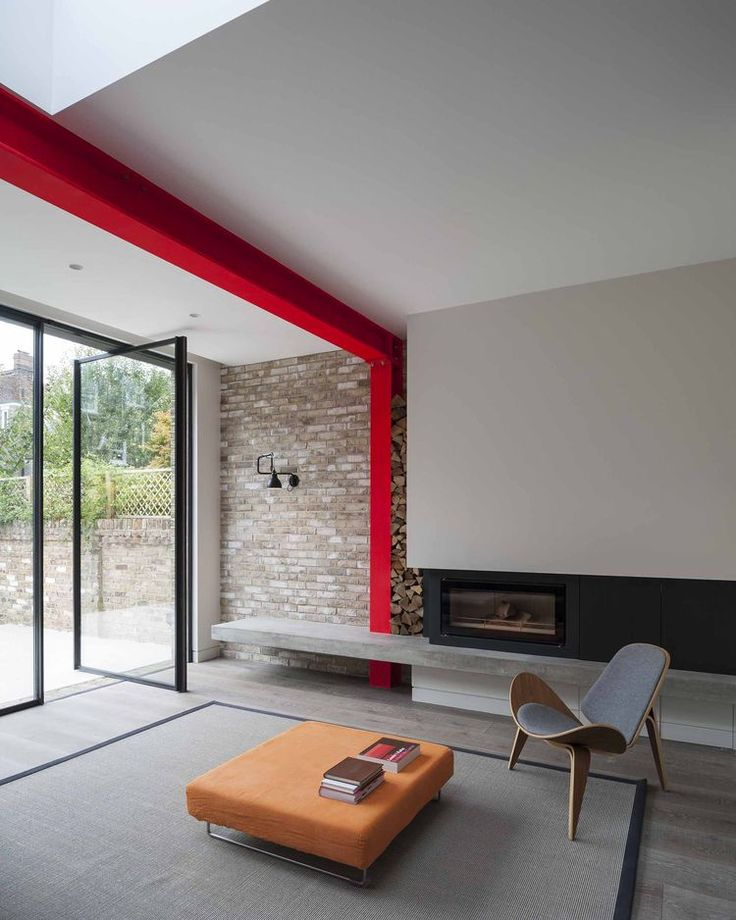 A Hans Wegner Shell chair by Carl Hansen & Søn outfits the living room, which is defined by a steel beam painted sharp red