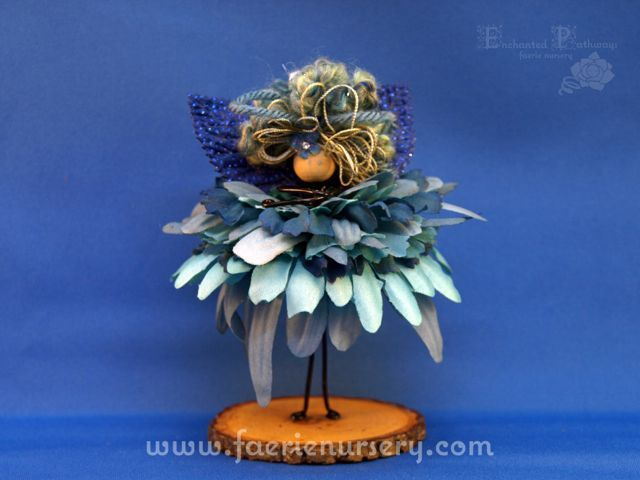 """Please meet Agua of the Northern Faeries Line.   Agua comes as a numbered edition - ordered by request only.  Agua stands just over 5"""" in height. She has a blue metallic wired body with a translucent heart shaped pony bead as a bodice. Her dress is made from 11 layers of silk flower petals in..."""