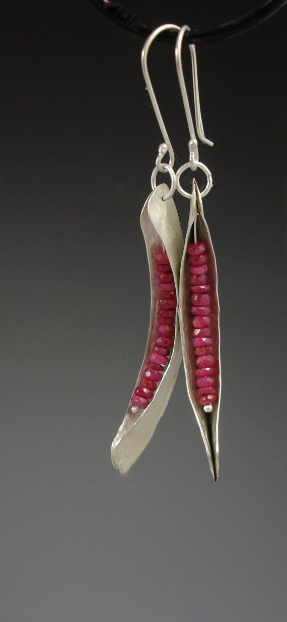 "These earrings are silver fold-formed danglers with  ruby ""seeds"""
