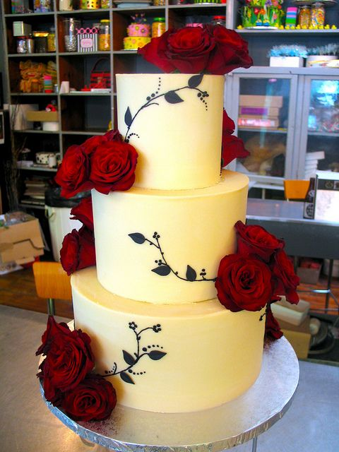 3-tier Wicked Chocolate wedding cake iced in white chocolate ganache decorated with red roses & delicate black piped branches & leaves by Charly's Bakery, via Flickr