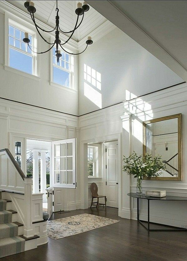 I like how they broke up the white walls and the tall ceilings in the two-story entry hall with stained-wood trim: