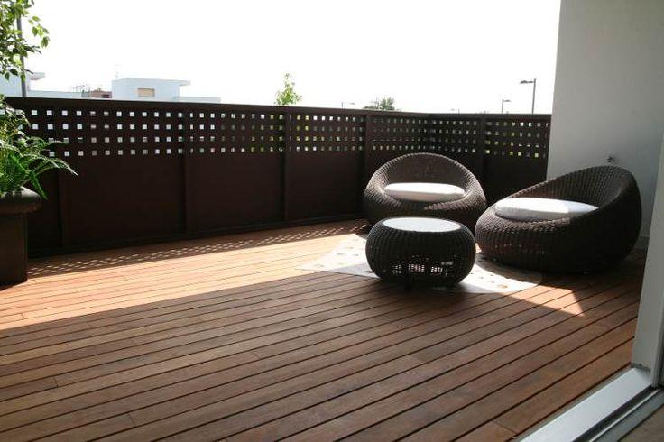 Terrazza con pavimento in teak e poltroncine in rattan