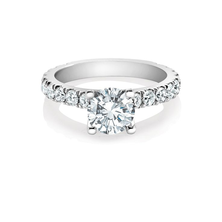 A band of round brilliant diamonds, dramatically set, compliments this dazzling Amira engagement ring. The open wall setting adds spirit, fire and an opulent sense of style.