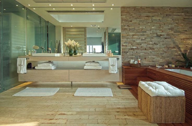 COMPLEMENTA LA HABITACIÓN de los padres una sala de baño tipo spa, en donde la combinación de las piedras naturales con la madera y el vidrio templado crean un ambiente sofisticado y funcional con tina con jacuzzi y ducha.