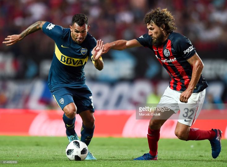 Carlos Tevez of Boca Juniors fights for ball with Fabricio Coloccini of San Lorenzo during a match between San Lorenzo and Boca Juniors as part of the Superliga at Pedro Bidegain Stadium on February 4, 2018 in Buenos Aires, Argentina.