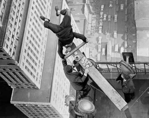 "Alvin ""Shipwreck"" Kelly, flag pole sitter, is fed donuts while positioned in a headstand on top of the Chanin Building in New York City, 1939"
