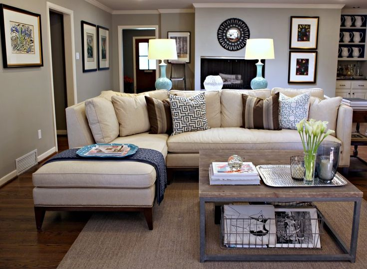 Love this lighter tan/neutral sectional. Blue accent lamps on a couch table behind link to the dark blue throw pillows, restoration hardware / industrial coffee table, neutral colored rug, nice large uniform picture frames as wall art, average sized living room, small living room, under techie coffee table magazines