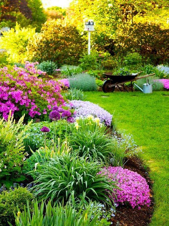 Charming Curves...mulch keeps weeds down and conserves moisture. Curved flowerbed border. Plants chosen in mostly similar hues. Round paving stones lead visitors through the grass border. Hardscape structures - tall birdhouse adds whimsy with function.