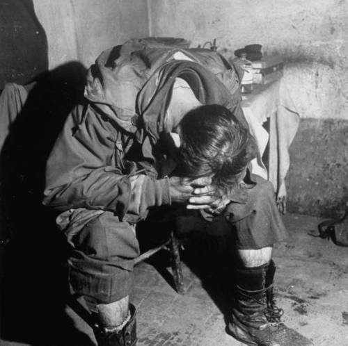 As photographed by the legendary Margaret Bourke-White, an exhausted US infantryman sits in an aid station, hunched over and sleeping. The soldier had been out in a night raid behind enemy lines somewhere along the Italian front in the Appennine Mountains where German forces still resisted, April 1945.