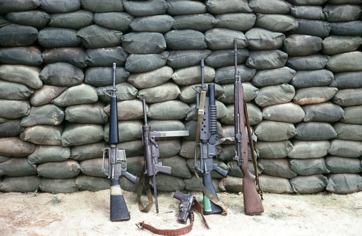 """Displayed weapons, from left to right, M16, M3 """"grease gun"""", M1911, M16 with mounted M203 grenade launcher, M14."""