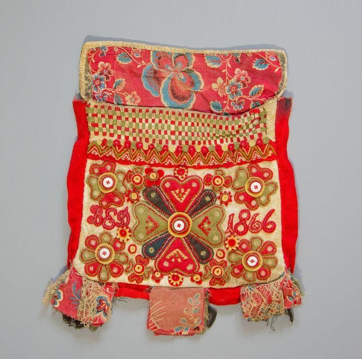 Kjolsäck till dräkt för kvinna från Rättviks socken, Dalarna. Modell med avskuret framstycke. Tillverkad av vitt rakat fårskinn med applikationer av ylletyg, kläde, i rött, grönt, mörkblått och gult. Centralt placerat hjärtmotiv med mindre blommotiv och rundlar runtom i ett tätt mönster. Broderier utförda med ylle- och bomullsgarner i flera färger, efterstygn, plattsöm, sticksöm. Dessutom fem knappar av porslin som mittmotiv i blommorna. Initialer klippta av rött kläde och applicerade: BSD…