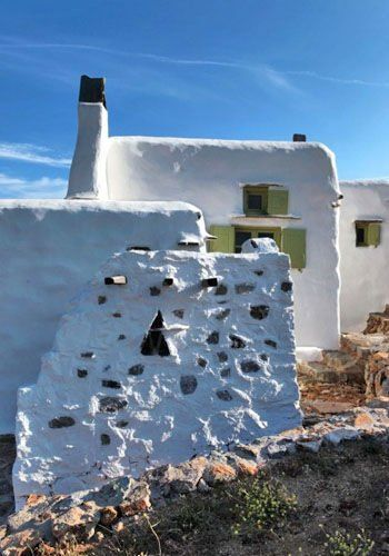 """Panormos to this day remains one of the """"hidden"""" areas of Mykonos thanks to its position on the northern side of the island and the rather unspoilt landscape. Perched on the hills surrounding the beach is a marvelous renovated 4 bedroom Cycladic property set in the most natural area of Mykonos."""