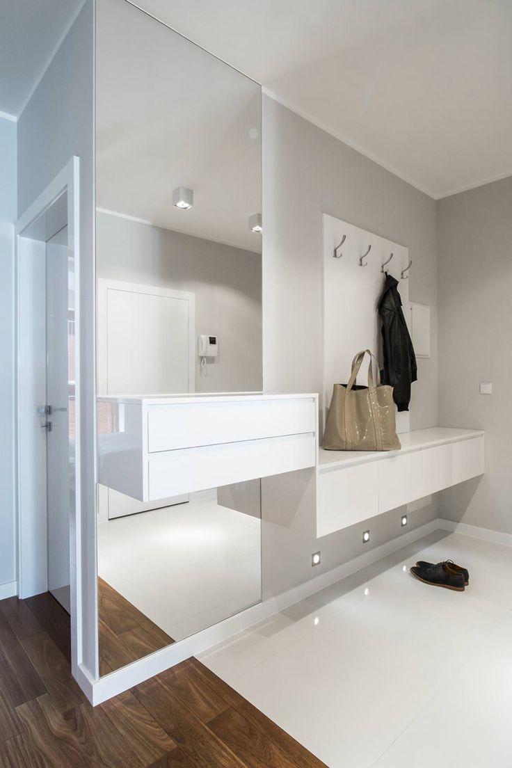 hellgraue Wandfarbe und raumhoher Wandspiegel ohne Rahmen, weiße Hängemöbel
