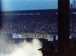 """THIS DAY IN ROCK HISTORY: July 12, 1979.  It's """"disco demolition"""" night.  Chicago WLUP DJs Steve Dahl and Gerry Meier host a bonfire of vinyl disco records at Cominskey Park.   The crowd got a out of hand and the White Sox had to forfeit the second game at the double header.   DJ Dahl came up with the idea after he was fired by a rival station when they switched to an all disco format."""