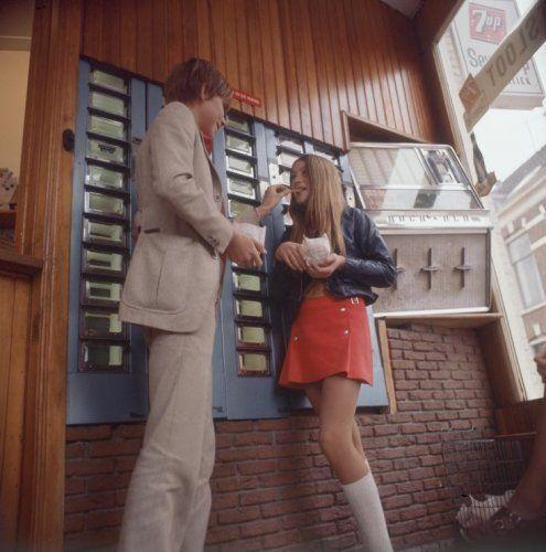 Jongen en meisje eten friet/patat uit een zakje, in snackbar/automatiek 'Zwetsloot' op de hoek Bakkerstraat/Esschilderstraat in Haarlem, Nederland 1968-1976. Let ook op de juke-box in de muur.