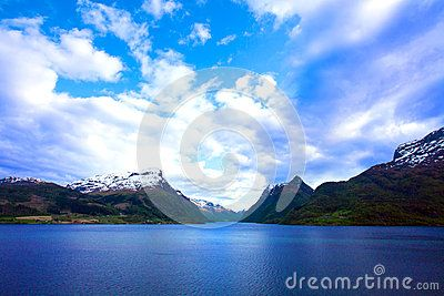 Blue waters of Great Lake in Norway with blue skies and sunshine against white clouds.