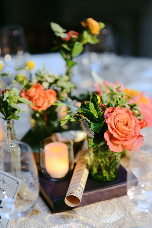 A coral rose, pink peony, and billy ball centerpiece