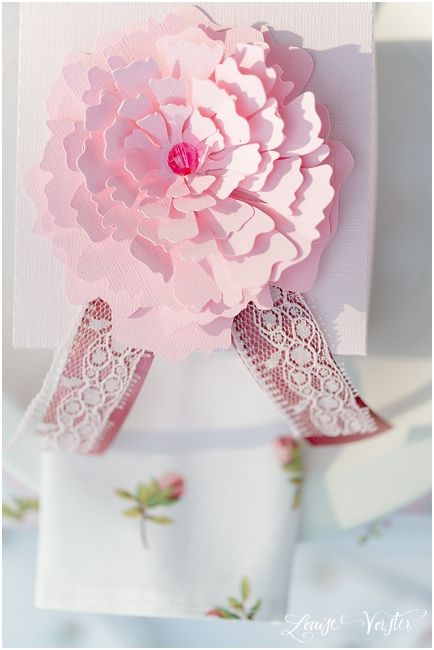 View from the top of pink invitation box with flower and different shades of pink lace and ribbon.
