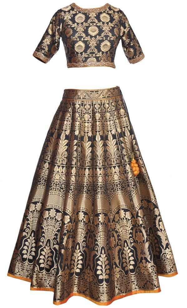 This set features a beautiful black brocade choli/blouse with gold kundan hand embroidery around the neckline, cuffs and at the bottom of the blouse an features a sheer keyhole back. It is teamed up with a full flared black lehenga in brocade base with dark orange silk border around the hem and also features a matching dori tie up with dark orange thread tasseled hangings. It comes with a contrast mustard net dupatta with black borcade border and pearl, gold kundan and sequins embellishe...