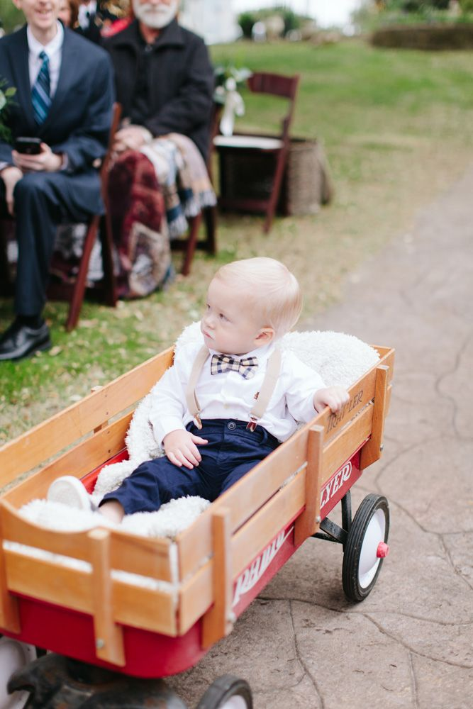 A young ring bearer is pulled down the aisle in a blanket lined wagon at an outdoor winter wedding in Texas // Jen Dillender Photography