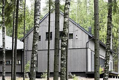 Lato-talon puiset ulkoseinät ovat ruskeanharmaata pystylaudoitusta.