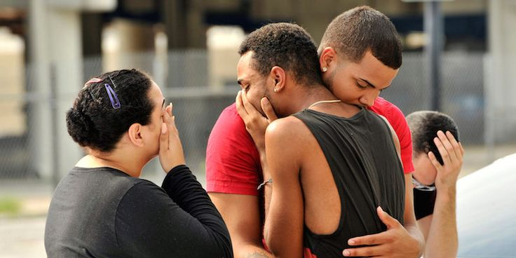 Friends and family members embrace outside the Orlando Police Headquarters…