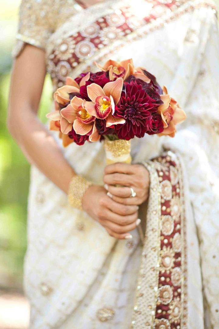 The palette of orchids, dahlias, and roses of Rana's bouquet reflect the embroidered crimson and golden tones of her saree. #weddingbouquet Photography: Mi Belle Photographers. Read More: http://www.insideweddings.com/weddings/elegant-red-gold-wedding-in-chicago-illinois/366/