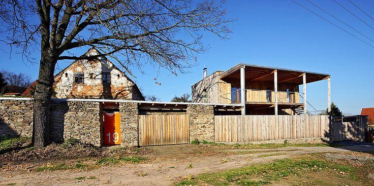 Dřevěná rámová konstrukce i dřevěné oplocení si dobře rozumí s původním kamenným zdivem.