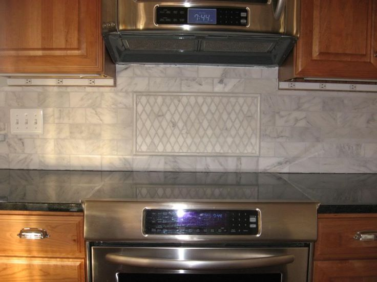 Carerra Marble And Black Backsplash