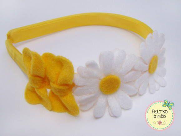 Tiara infantil revestida com viés de cetim amarelo, decorada com duas margaridas e dois laços amarelos de feltro. R$ 13,50