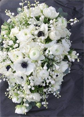Anemones, Ranunculas, delicate Lilly of the Valley and Gypsophila arranged in a trailing bouquet.