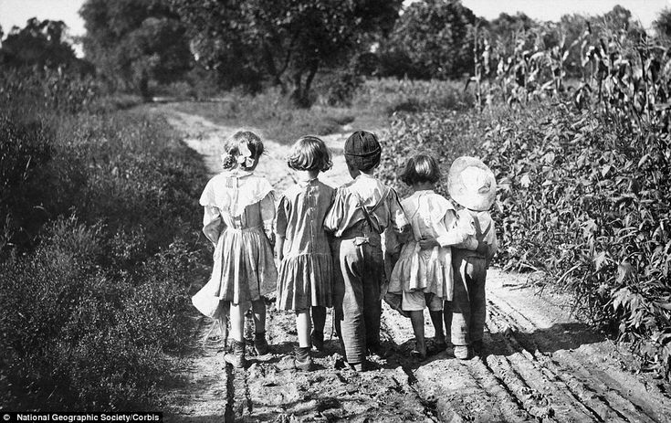 Arm in arm: Young children hold on to one another as they walk down a dirt road alongside a corn field in Pennsylvania, USA, in 1919